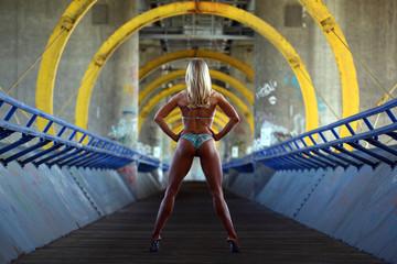 Sexy female bodybuilder in bikini standing on a bridge