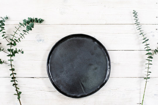 Top view empty black plate on rustic wooden table. Ceramic black plate on white wooden background with free space. Flat lay of handmade black dish on white wooden table.