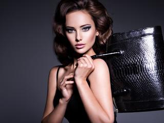 Beautiful woman with brown hair holds black handbag