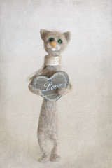 Felted wool toy.Woolen handmade toy cat with a wooden heart.