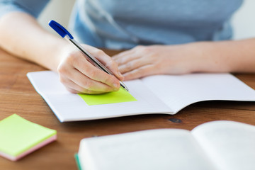 close up of student with book and notebook at home