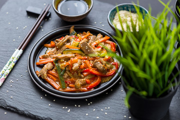 Chinese Cuisine - Pork with Vegetables Deep Fried in Sour-Sweet Sauce on Dark Background