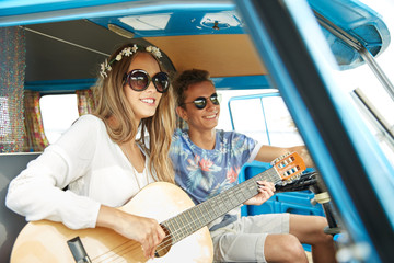 smiling hippie couple with guitar in minivan car
