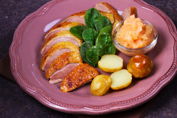 Spiced slow roast duck, apple sauce, spinach and potato, served on pink plate