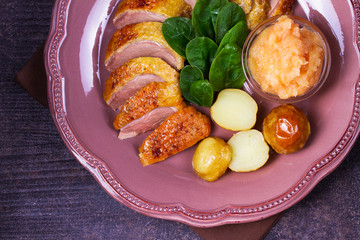 Spiced slow roast duck, apple sauce, spinach and potato, served on pink plate. View from above, top studio shot