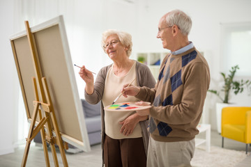 Elderly couple painting on a canvas