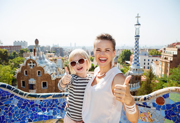 Smiling mother and baby at Park Guell showing thumbs up