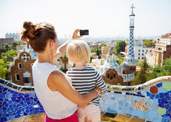 Mother and baby taking photos with digital camera at Park Guell