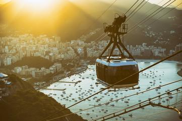 Sunset view from Sugarloaf Mountain (Pão de Açucar) with a bonde cable car gondola against the Rio de Janeiro, Brazil city skyline