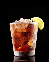 Cold cola with ice in a glass on a black background