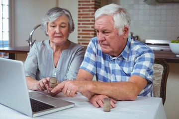 Senior couple searching pills with help of laptop
