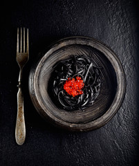 black pasta with red caviar on a black background