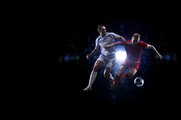 Soccer players in the air over black background
