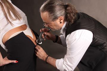 Mann hilft Frau beim Anziehen des Rock mit Kneifzange