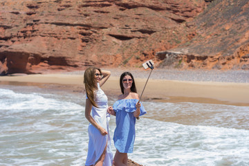 Two young beautiful women make selfie on the beach with rocks background.