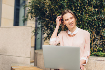 Beautiful woman sitting on the bench, watching to her laptop