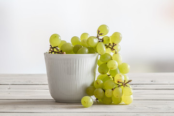 White bowl with green grapes