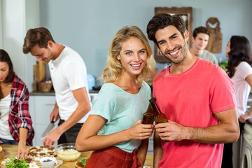 Portrait of smiling young couple toasting beer bottles at home