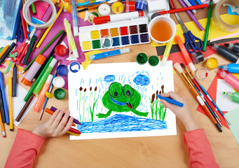 child drawing frog in river, top view hands with pencil painting picture on paper, artwork workplace
