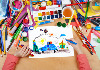 child drawing police car and helicopter, top view hands with pencil painting picture on paper, artwork workplace