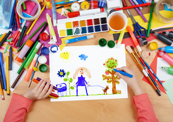 child drawing walking girl with dog, top view hands with pencil painting picture on paper, artwork workplace