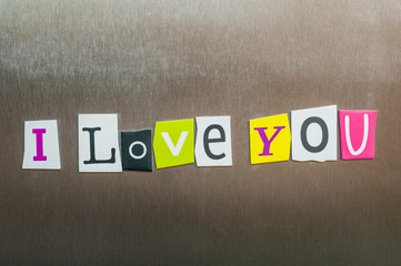 I Love You written with color magazine letter clippings on metal background. Design for relationships, romance, love and Valentines day