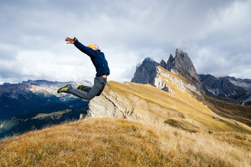 A young boy jumps for joy in scenic mountains