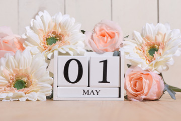 May 1st. Image of may 1 white block calendar on white background with flowers. Spring day, empty space for text. International Workers' Day