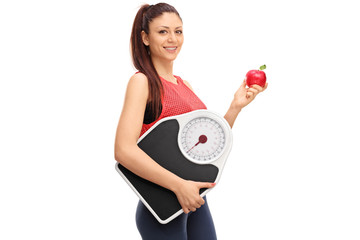 Woman holding an apple and a weight scale