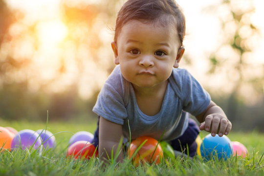 Cute asian baby crawling in the green grass and colorful ball