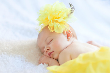 Newborn girl is sleeping in yellow skirt with hat