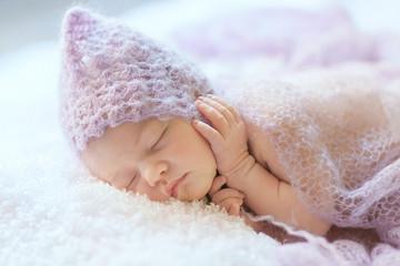 Newborn girl is sleeping in violet hat. Sleeping time.