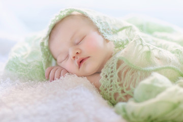 Newborn girl is sleeping under green cover. Sleeping time.