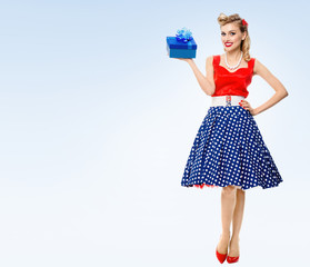 Full body of woman in pin-up style dress with gift box