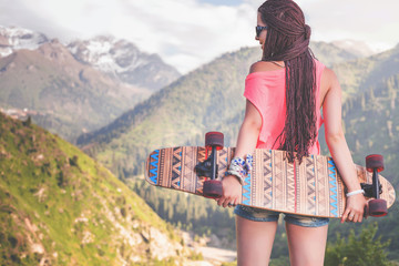 Fashion teenage girl with longboard skateboard at mountain