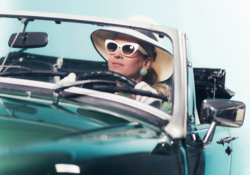 Woman in retro 1960s fashion with hat and shades driving convert