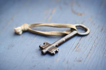 Old metal key on blue background.