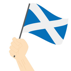 Hand holding and raising the national flag of Scotland