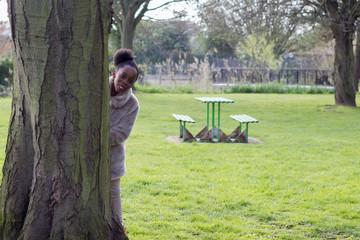 Little girl peeps around the tree