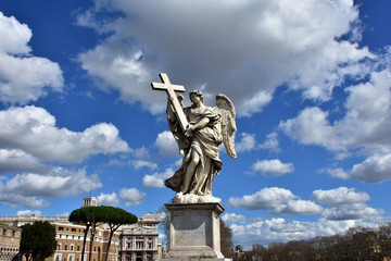 Angel with the Holy Cross and beautiful sky in Rome. Marble statue of angel from Sant'Angelo bridge monumental balustrade.