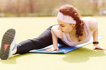 Young flexible woman stretching on fitness mat