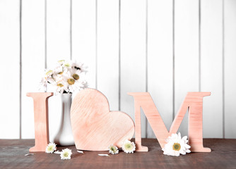 I love mom inscription made of wooden letters with heart on light background