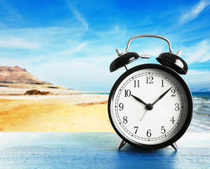 Summer time concept. Alarm clock on wooden table on beach background