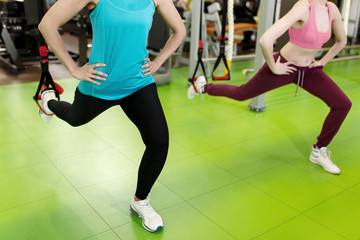 Two womans does suspension training with fitness straps in gym