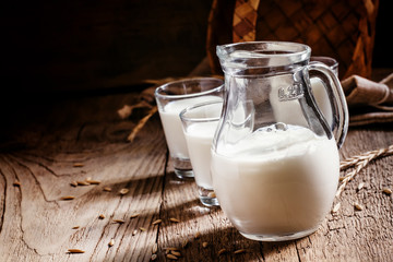 Fresh cow's milk in glass jug, vintage wooden background, still