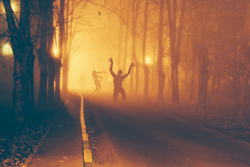 Several zombie on the street at night.