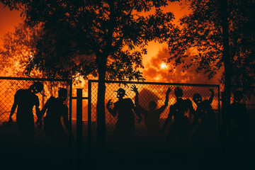 Several zombie behind a mesh fence at night.