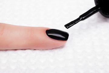 Manicure - Beautiful manicured woman's nail with black nail polish