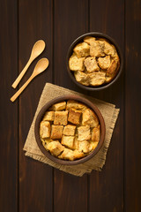 Bread pudding made of diced bread, milk, egg, cinnamon, sugar and butter, photographed on dark wood with natural light