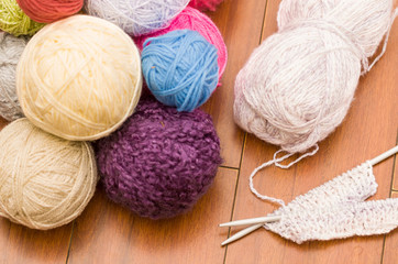 White, purple, blue and pink yarn balls piled up on wooden surface with knitting needles next to it, as seen from above